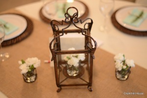 wrought iron lantern rustic wedding centerpiece with miniature white carnations and burlap