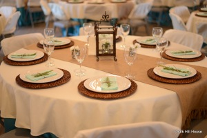 Wrought Iron Lantern wedding table setting with burlap runner, rattan chargers, and teal satin tablecloths